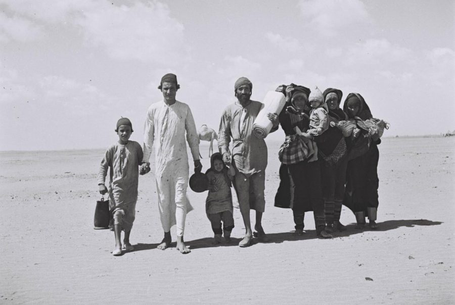A Jewish-Yemenite family is walking through the dessert to a receiving camp set up by the